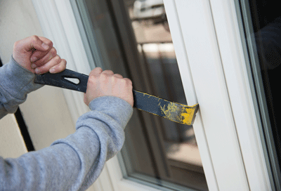 Image of someone breaking into a window with a crowbar