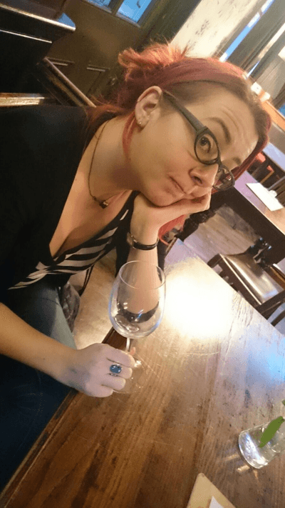Rachel England holding an empty glass of wine
