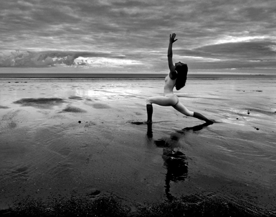 Image of a woman doing yoga on the beach
