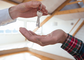 A landlord handing over keys to a new tenant