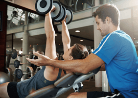 Image of a woman at the gym with a personal trainer
