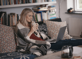 A woman wrapped in a blanket on a laptop