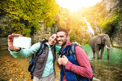 Image of a couple taking a selfie with an elephant