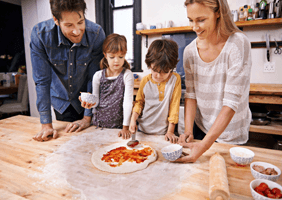 Image of a family enjoying cooking a pizza together