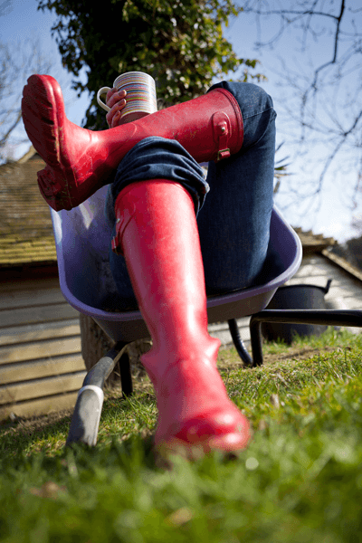 Someone sitting in a wheelbarrow, wearing wellies and drinking a cup of tea