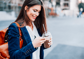 Image of a woman smiling at her phone