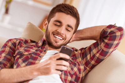 Image of a man really enjoying playing on his phone