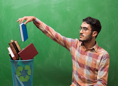 Image of a man putting a book in a bin nonchalantly