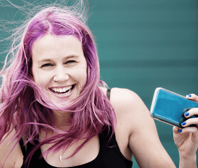 Image of a woman with purple hair using her phone