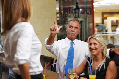 Image of a man with an imposing moustache calling over a waitress