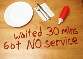 Image of 'waited 30 mins, got no service' written in ketchup on a table