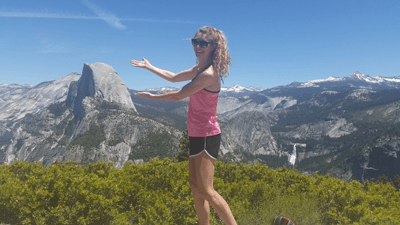 Image of Abbie Laughton-Coles gesturing to the view at Glacier Point