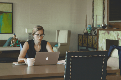 Image of a woman at a desk with a laptop