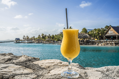 Image of a cocktail infront of a beach