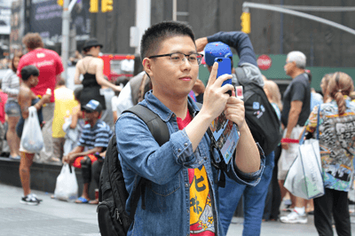 Image of a tourist taking a picture in a city