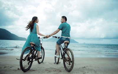 Image of a couple holding hands while cycling on the beach