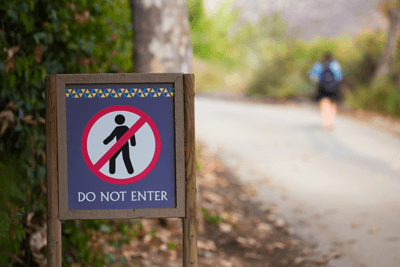 Image of someone walking past a 'Do not enter' sign