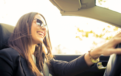 Image of a woman enjoying driving a car