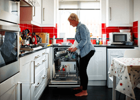 Woman unloading a dishwasher