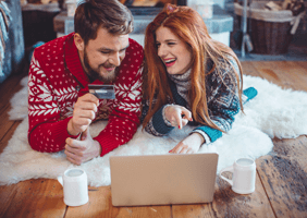 A couple in Christmas jumpers with a credit card