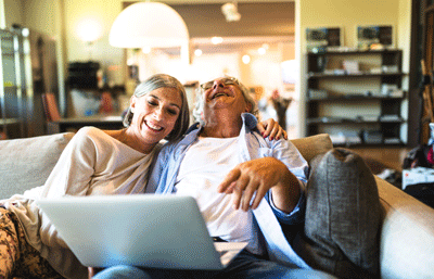 Image of elderly couple laughing and looking at a computer