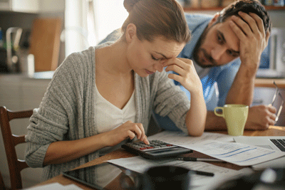 Image of couple looking worried at bills
