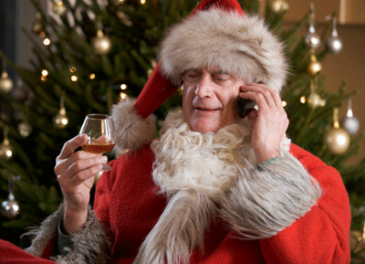Image of a santa chilling out with a sherry on his phone