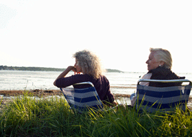 Image of a woman and her mum sitting on a beach