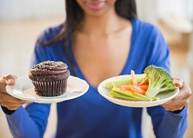 Image of woman holding two plates one with healthy vegetable the other wth a chocolate muffin