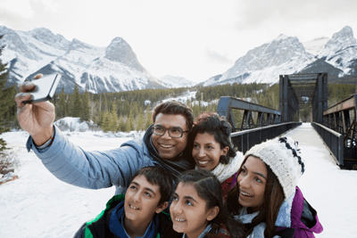 Image of family taking a selfie on a snowy mountain