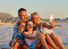 Image of family taking a selfie on a beach