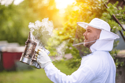 An image of a beekeeper with a smoker