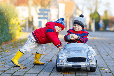 An image of two toddlers playing in the winter in a toy car
